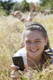 A young girl on the phone. Sitting in a field of long grass Royalty Free Stock Photo