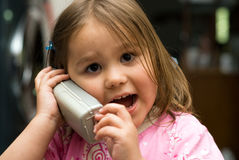 Young Girl On The Phone. Little girl talking on the phone inside the house Royalty Free Stock Photography
