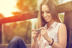 Young girl with phone outdoor Royalty Free Stock Photos