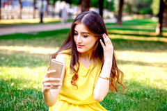 Young girl with phone in park at summer Stock Images