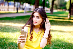 Young girl with phone in park at summer Royalty Free Stock Images