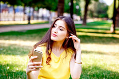 Young girl with phone in park at summer Stock Photo