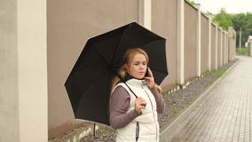 Young girl with phone under umbrella in rainy day. Girl in a white waistcoat under a black umbrella stands on the background of a high stone fence in the rain stock video footage