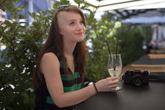 Young girl with photo camera in  a caffe enjoying summer. Young girl writing in a caffe with glass of lemonade Stock Images