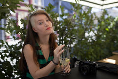 Young girl with photo camera in a caffe enjoying summer. Young girl writing in a caffe with glass of lemonade stock image