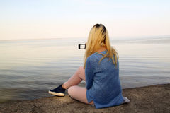 Young girl photographed on a mobile phone sitting on the shore Royalty Free Stock Photo