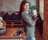 Young girl photographer dressed in a gray elegant jacket cup holding of takeaway coffee while leaning on a table in a. Portrait of a young girl photographer stock photos