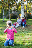 Young girl photographing with cellphone, family sitting on grass on background Stock Images