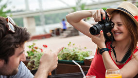 Young Girl Photographing Cheerful Man Stock Photo