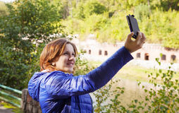 Young girl photographing herself a mobile phone Royalty Free Stock Images