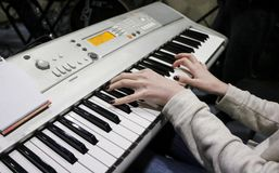 A young girl pianist plays the electronic piano with her favorite music. Female graceful hands touch the keys of the synthesizer c stock photos