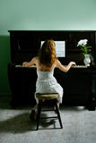 Young girl and piano at home Stock Image