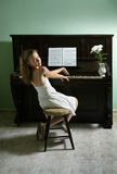 Young girl and piano at home Stock Images