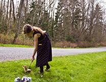 Young Girl Picking up Litter with a Stick. 8 year old Caucasian child is picking up litter on the side of the road with a stick.  She's trying to practice good Royalty Free Stock Images