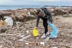 Young Girl Picking Up Trash From the Beach. stock photography