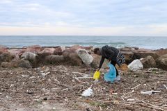 Young Girl Picking Up Trash From the Beach. stock image