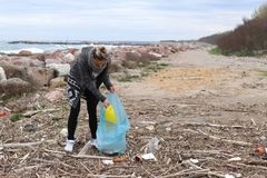 Young Girl Picking Up Trash From the Beach. stock photo