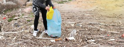 Young Girl Picking Up Trash From the Beach. royalty free stock photos