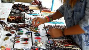 A young girl picks in the market and trying beads stock footage