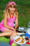 Young girl on the picnic. Young girl sitting on the blanket  on the picnic with plate of pancakes Royalty Free Stock Image