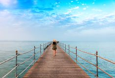 Young girl on the pier. Young girl in straw hat waking on the pier. Vacation theme Stock Image