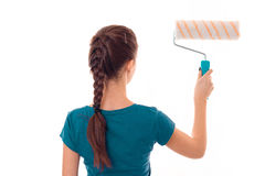 Young girl with pigtail worth turning backwards and holding a roller for painting Stock Photos