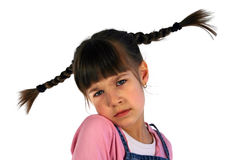 Young Girl with Pigtails. Frowning girl with braided pigtails flying out in the air Royalty Free Stock Photos