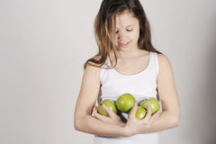 Young girl with a pile of apples Royalty Free Stock Image