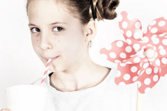 Young girl with a pin wheel and fresh drink Stock Photo