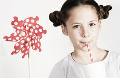 Young girl with a pin wheel and fresh drink Royalty Free Stock Photo