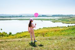 Young girl with a pink ball on the lake while walking in the nat stock photo
