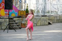 A young girl in pink is dancing. Smiling dancing. Dancing in the street. In the costume dancing stock photography