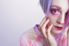 Young girl with pink eyes and hair bit her lip. A young girl with pink eyes and hair, like a doll stock photography