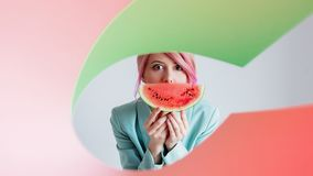 Young girl with pink hair in formal clothes of the 80s with a slice of watermelon with green nad pink paper. Portrait of a young girl with pink hair in formal stock photography