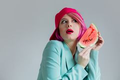 Young girl with pink hair in formal clothes of the 80s with a slice of watermelon. Portrait of a young girl with pink hair in formal clothes of the 80s with a royalty free stock photos