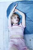 A young girl in a pink home suit near a soft chair. Beautiful model poses for fashion magazine. Picture in calm gray-blue tones Royalty Free Stock Photography
