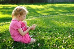 Young girl in pink picking up flowers in a field Stock Images