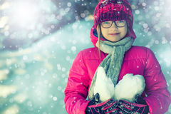 Young girl in pink playing on snow. Royalty Free Stock Photography