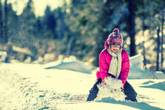 Young girl in pink playing on snow. Stock Photo