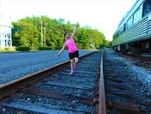 Young Girl In Pink On Railroad Tracks Stock Photo