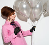 Young girl in a pink raincoat with balloons Stock Image
