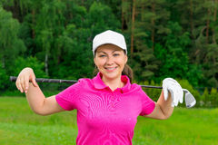 Young girl in a pink shirt and a white baseball cap. With a golf club Stock Image