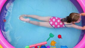 Young girl in pink swimsuit playing in colorful rainbow inflatable swimming pool backyard. Summer active lifestyle swim