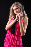 Young girl with pistol. On a black background Royalty Free Stock Image