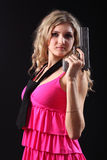 Young girl with pistol. On a black background Stock Photos