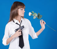 Young girl with pistol and flower in a hands Royalty Free Stock Photography