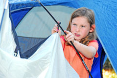 Young girl pitching tent Stock Images