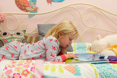 Young Girl in PJ`s Reading a Storybook in Bed Royalty Free Stock Images