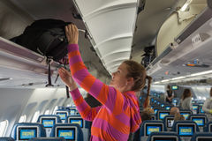 The young girl placed her hand luggage. Into the compartment on the plane Royalty Free Stock Photo