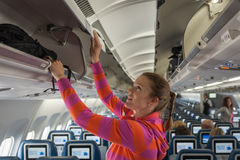 The young girl placed her hand luggage. Into the compartment on the plane Stock Images